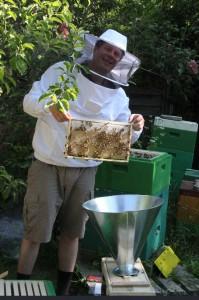 Ein stolzer Imker mit einer Honigwabe