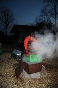 Eine Zarge wird in die kochende Lauge getaucht.